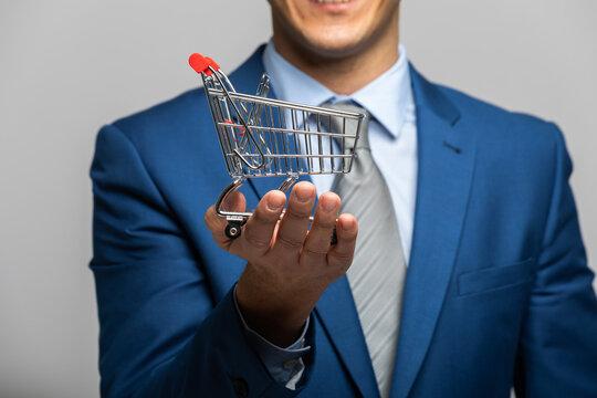 Businessman holding a mini shopping cart