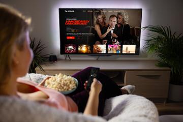 Fototapeta Woman watching TV series and movies via streaming service at home obraz