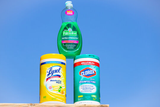 Toronto, Ontario Canada - April 2020: A bottle of Palmolive soap, Lysol and Clorox disinfectant wipes against blue sky background. Household cleaning products for prevention of Coronavirus.