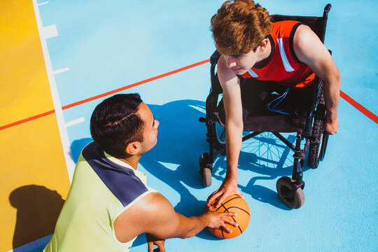 latin young man using wheelchair and playing basketball with a friend in Mexico, disabled people