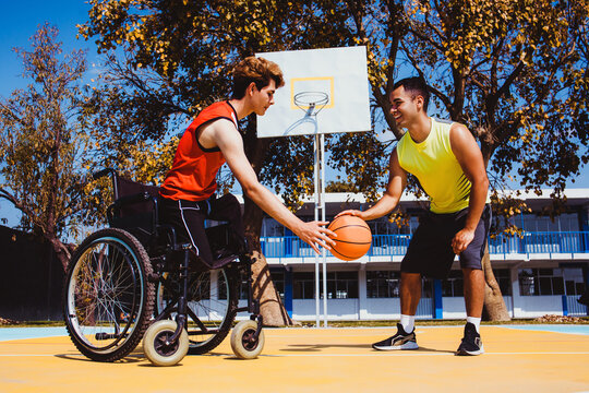 latin young man using wheelchair and playing basketball with a friend in Latin America disabled person