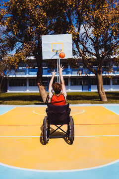 latin young man using wheelchair and playing basketball disabled person