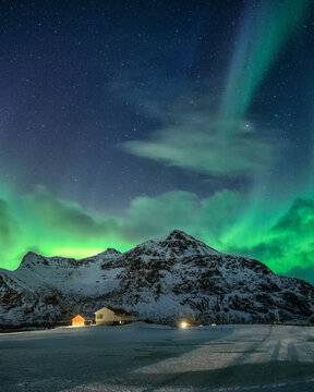 Aurora Borealis with starry over snowy mountain and nordic village at night in Flakstad, Lofoten Islands