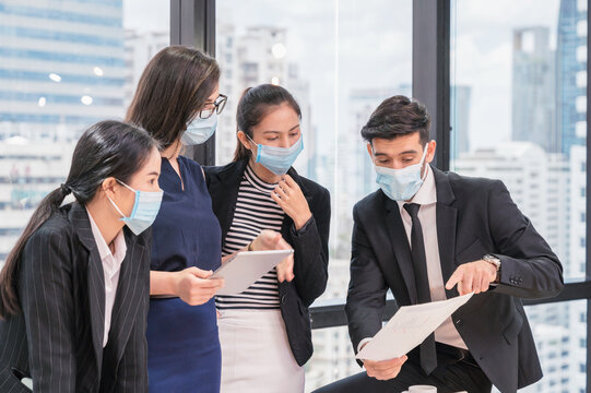 Group of multiethnic business colleague meeting and discussing on corporate business plan in the office. Team of business people wearing face mask during consultation