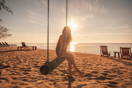 Young asian woman relaxing on wooden swing on the beach in the sunrise