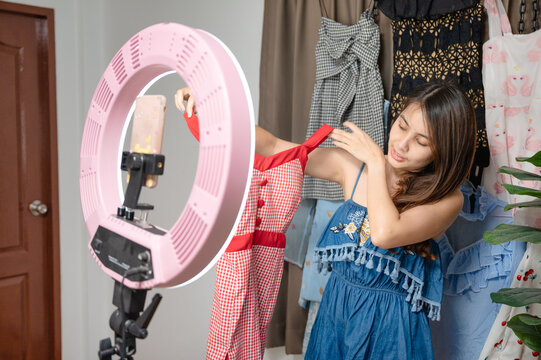 Young asian woman selling clothes online live streaming by smartphone in the house