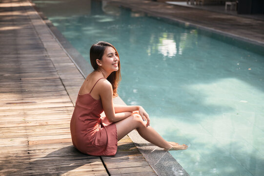 Young asian woman in dress sitting by swimming pool at tropical resort