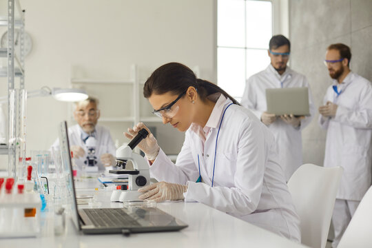 Virologist doing research studying in medical laboratory. Concentrated female virologist in goggles and latex gloves sits at table in laboratory and examines cells under microscope.