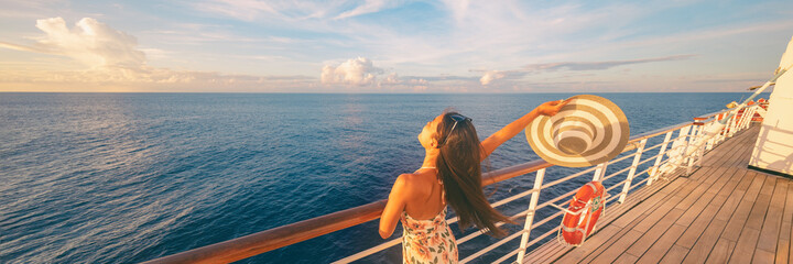 Obraz Happy cruise woman relaxing on deck feeling free watching sunset from ship on Caribbean travel vacation. Panoramic banner of sea and boat. - fototapety do salonu