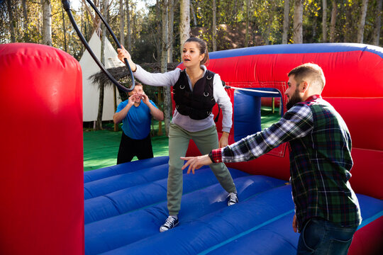 Excited male and female friends having fun passing obstacle course at adventure park