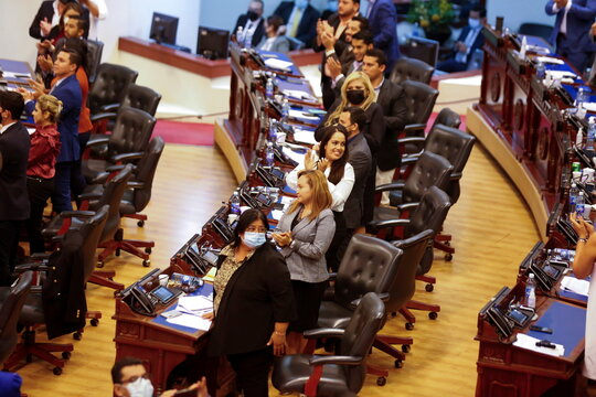 Representatives of the Nuevas Ideas party applaud after voting to approve a loan to finance government programs during a session of The Salvadoran Congress, in San Salvador
