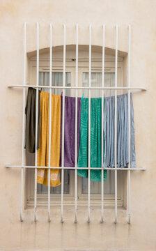 fenêtre avec des barreaux de prison derrière lesquels du linge est en train de sécher