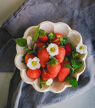 Erdbeere mit Minze und Blüten in einer Schale aus japanischer Keramik
