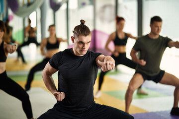 Dedicated athlete practicing martial arts while working out with group of people at health club.