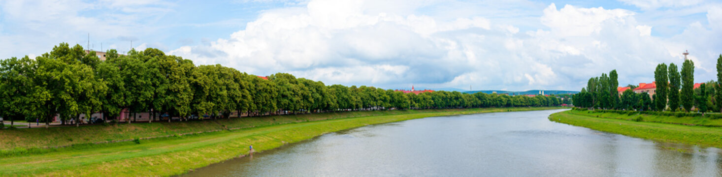 panorama of river uzh between linden and chestnut alleys on the nezalezhnosti and kyiv embankments. popular travel destination. beautiful urban scenery on a sunny day