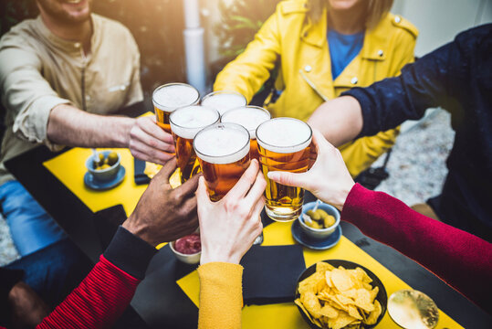 Group of multicultural friends drinking and toasting beer at brewery bar restaurant - Happy people having fun at rooftop home party - Focus on glasses