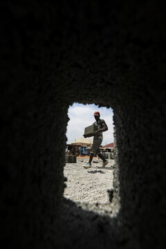 A man carries a moulded block at a block making centre in Abuja