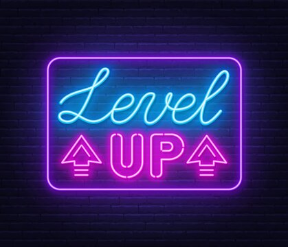 Level up neon sign on brick wall background.
