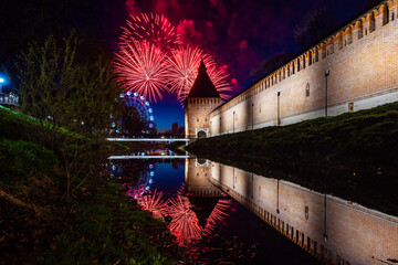 volleys of festive fireworks are reflected in the water. salute to the city holiday. beautiful view of the pond and the old fortress under the fireworks flashes
