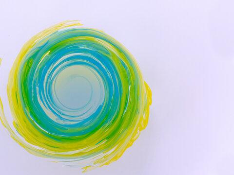 水中の絵の具 回転して輪を作る青と黄色