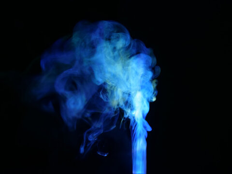 Abstract color series. Composition of colorful smoke in motion. Fusion of neon blue mist isolated on a dark background to inspire creativity.