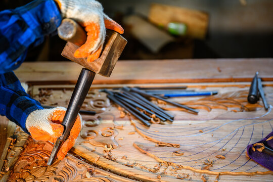 Asian male craftsman carved wood craftsmen use wooden hammers to shovel wood chisels tools carpentry work wooden background Engineers provide tree shapes.
