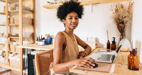 Fototapeta Female business owner working on laptop obraz