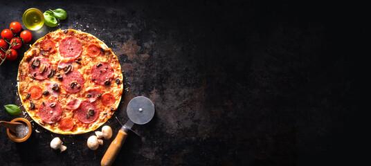 Fototapeta Crispy italian pizza with salami, ham, olives, tomatoes, peppers, cheese and mushrooms obraz