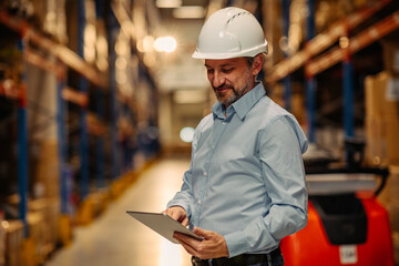 Fototapeta Mid adult manager using digital tablet in warehouse obraz