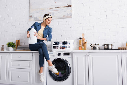 Cheerful housewife with detergent sitting near washing machine and clothes