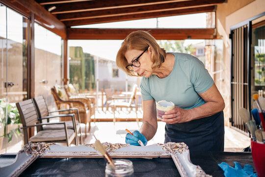 Blond senior woman painting frame at sun room