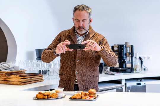 Mature man photographing fast food through smart phone while standing in kitchen at home