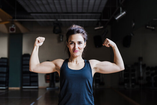 Beautiful female athlete flexing muscles in gym