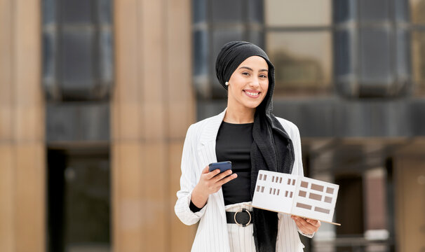 Smiling female architect with smart phone holding architectural model outdoors
