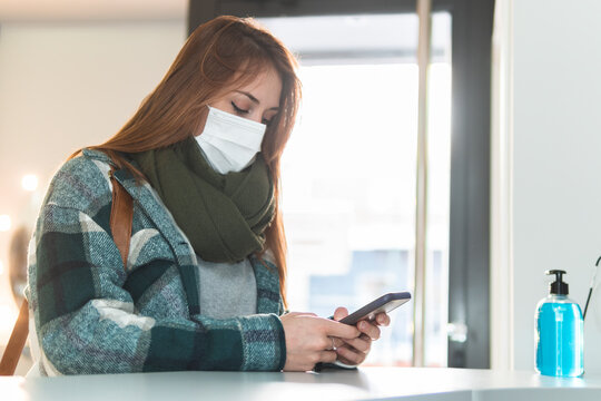 Portrait of young woman wearing protective face mask waiting in beauty salon lobby with smart phone in hands