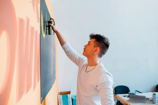 Young man spraying paint on black cardboard in studio