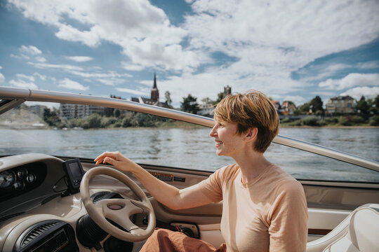Smiling woman driving motorboat while looking away