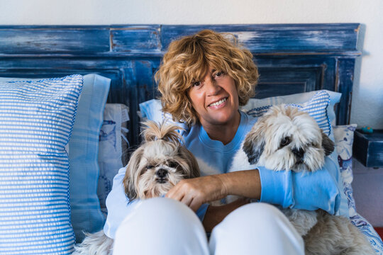 Smiling mature woman sitting with dogs at home