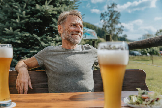 Smiling mature man looking away while sitting in beer garden