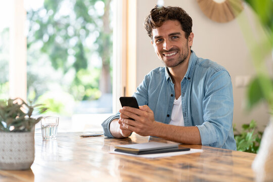 Smiling male freelance worker holding smart phone while sitting at table in home office