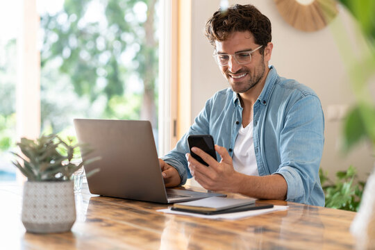 Smiling male freelancer with eyeglasses using smart phone while sitting with laptop at home office