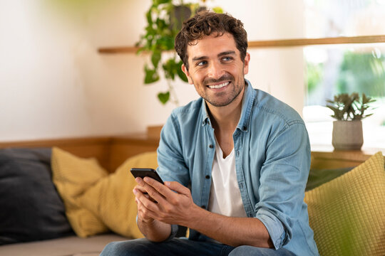 Smiling handsome man holding smart phone while sitting on sofa