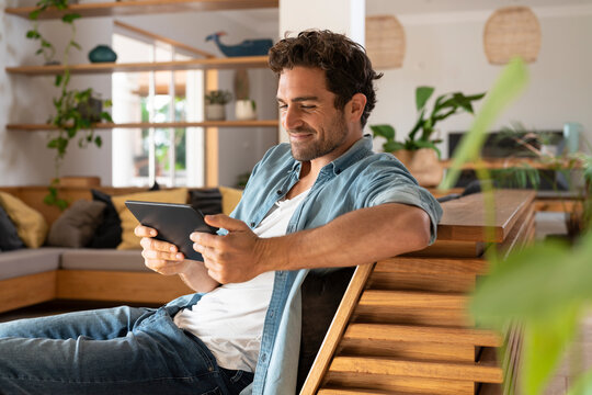 Smiling mid adult man looking at digital tablet while sitting on couch at home