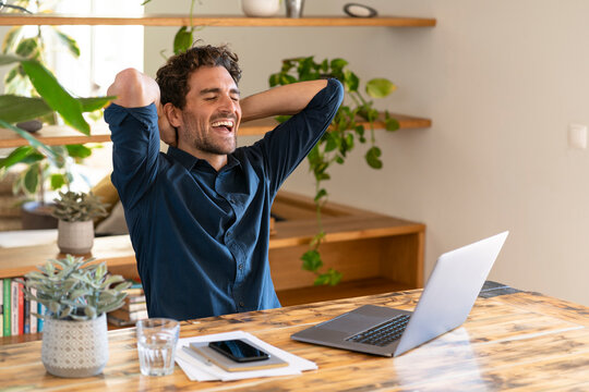 Happy male freelancer with hands behind head laughing while sitting in front of laptop at home