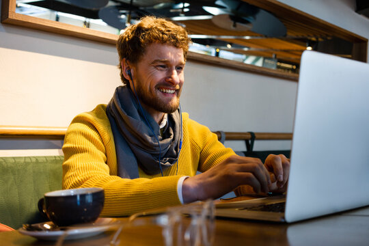 Happy male entrepreneur using laptop during video call at cafe
