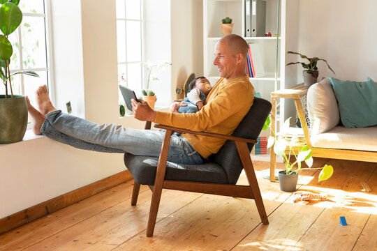 Smiling father using digital tablet and holding baby while sitting on armchair at home