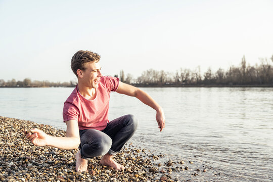 Cheerful young man throwing pebble in lake on sunny day