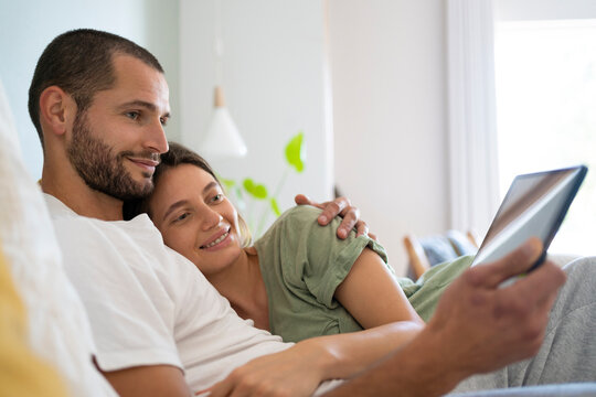 Young man embracing his girlfriend while using digital tablet at home