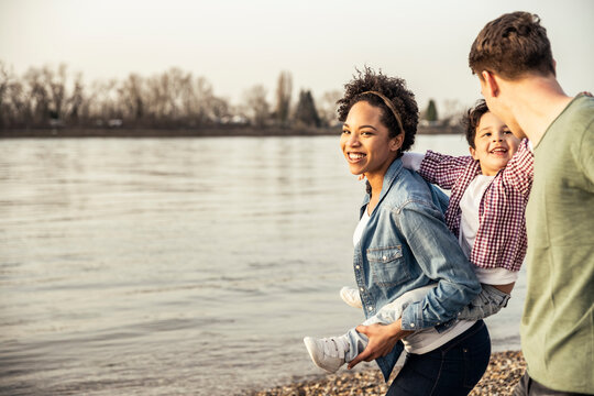 Smiling mother piggybacking son while walking with father by lake
