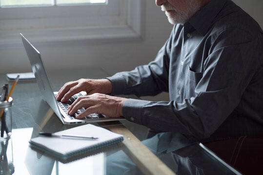 Senior male business professional working on laptop at table